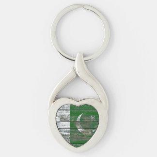 La bandera paquistaní en la madera áspera sube a llavero plateado en forma de corazón