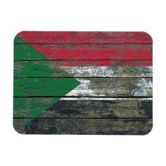 La bandera sudanesa en la madera áspera sube a imanes de vinilo
