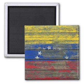 La bandera venezolana en la madera áspera sube a iman de nevera