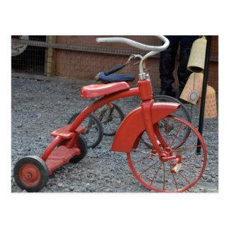 La bici roja del triciclo del vintage deja paseo tarjetas postales