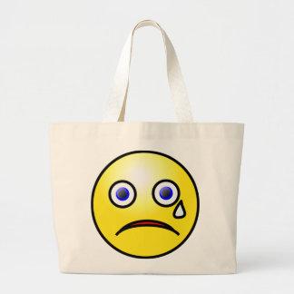 La bolsa de asas amarilla triste de la cara