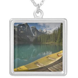 La canoa parqueó en un muelle a lo largo del lago  colgantes