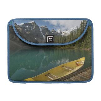 La canoa parqueó en un muelle a lo largo del lago  fundas para macbook pro