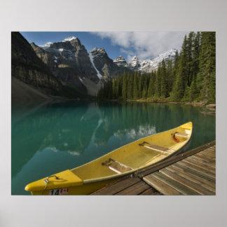 La canoa parqueó en un muelle a lo largo del lago  posters
