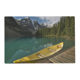 La canoa parqueó en un muelle a lo largo del lago tapete individual