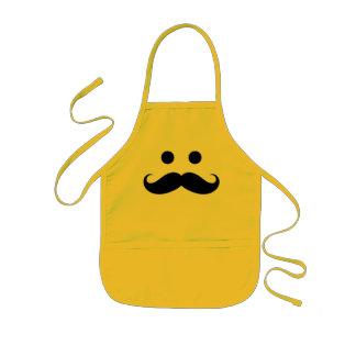 La cara sonriente del bigote divertido embroma el  delantal infantil