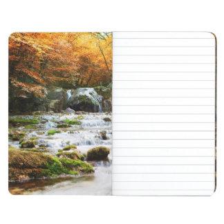 La cascada hermosa en el bosque, otoño cuaderno grapado