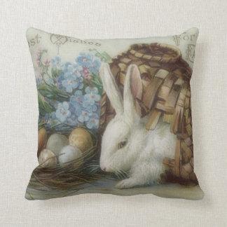 La cesta pintada coloreada del huevo del conejito  cojín