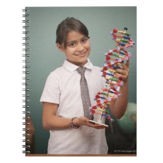 La colegiala joven lleva a cabo un modelo colorido cuaderno