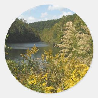 La corriente de la montaña se convierte en lago pegatina redonda
