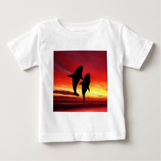 La danza de las ballenas en la puesta del sol playera de bebé