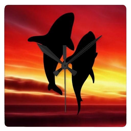 La danza de las ballenas en la puesta del sol relojes