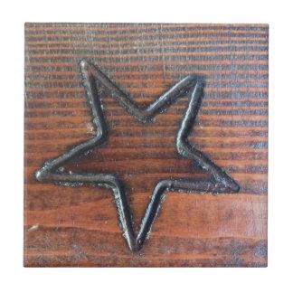 La estrella rústica quemó en el pirograbado de mad azulejo cuadrado pequeño
