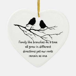 La familia tiene gusto de ramas en un árbol que adorno navideño de cerámica en forma de corazón