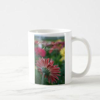 La flor rosada de la margarita del Gerbera cita lo Tazas