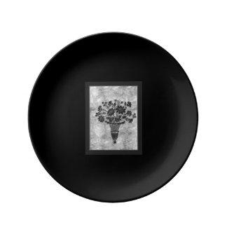 La flor siluetea la placa de plata del pan por platos de cerámica