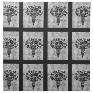 La flor siluetea las servilletas de cena de plata