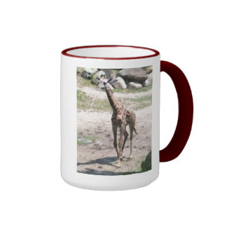 La foto de una jirafa del bebé que camina en taza de dos colores