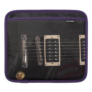 La guitarra eléctrica negra del Grunge ata la caja Mangas De iPad