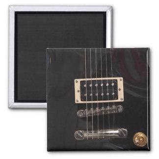 La guitarra eléctrica negra elegante ata el primer imán cuadrado