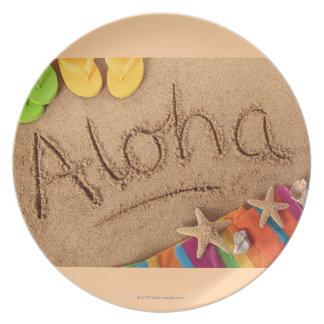 La hawaiana de la palabra escrita en una playa are plato para fiesta