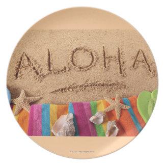 La hawaiana de la palabra escrita en una playa are plato de cena