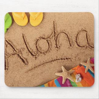 La hawaiana de la palabra escrita en una playa are tapete de ratones