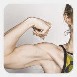 La hembra rubia joven dobla el músculo del bíceps pegatina cuadrada