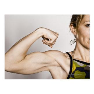 La hembra rubia joven dobla el músculo del bíceps tarjeta postal