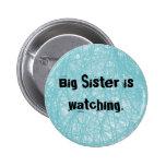 La hermana grande está mirando. Botón azul redondo