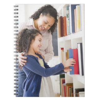 La hija de ayuda de la madre elige el libro en est libreta