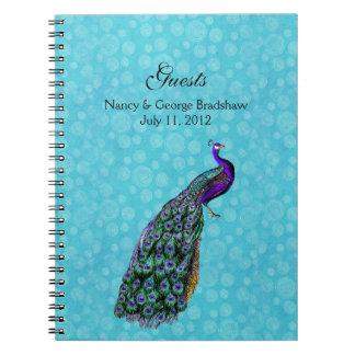 La huésped colorida del boda del pavo real firma a libro de apuntes con espiral