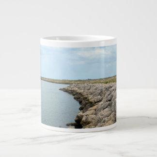 la isla curvada de la barrera de la roca en la taza grande