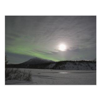 La luna sube sobre la cortina de los borealis postales