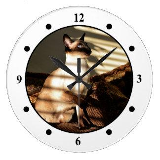 La luz del sol sombrea el gato siamés reloj redondo grande