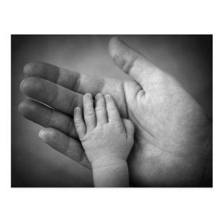 La mano del bebé de la postal en mano de las madre
