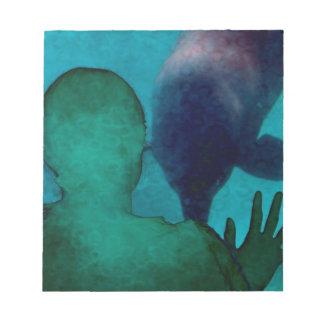 La mano del chica encima de delfínes apoya grunged libreta para notas