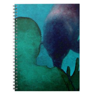 La mano del chica encima de delfínes apoya grunged libros de apuntes con espiral