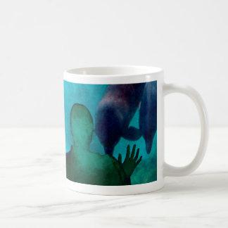 La mano del chica encima de delfínes apoya grunged taza básica blanca