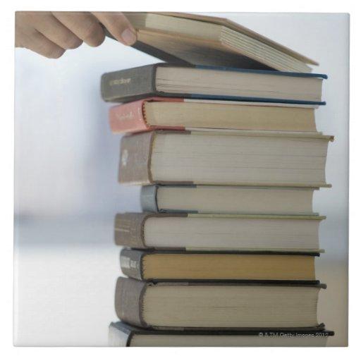 La mano del hombre que toma un libro de una pila d azulejos ceramicos