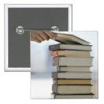 La mano del hombre que toma un libro de una pila d pin