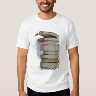 La mano del hombre que toma un libro de una pila d playeras