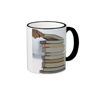 La mano del hombre que toma un libro de una pila d taza a dos colores