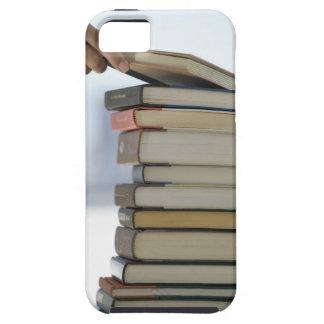 La mano del hombre que toma un libro de una pila iPhone 5 funda