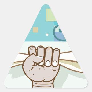La mano humana lleva a cabo un artículo de papel pegatina triangular