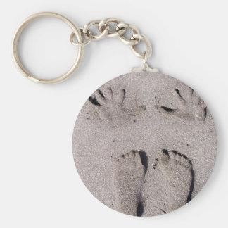 La mano y los pies imprime en arena de la playa de llaveros