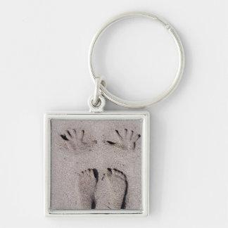 La mano y los pies imprime en arena de la playa de llavero cuadrado plateado