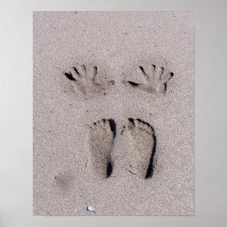 La mano y los pies imprime en arena de la playa de poster