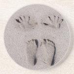 La mano y los pies imprime en arena de la playa de posavaso para bebida