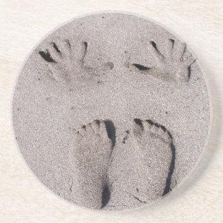 La mano y los pies imprime en arena de la playa de posavasos diseño